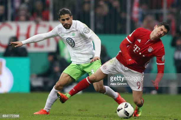 Robert Lewandowski of Muenchen is challenged by Ricardo Rodriguez of Wolfsburg during the DFB Cup Round Of 16 match between Bayern Muenchen and VfL...