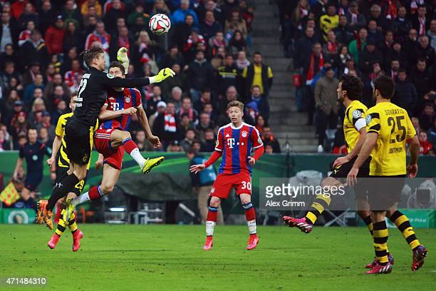 Robert Lewandowski of Muenchen is hit by goalkeeper Mitch Langerak of Dortmund during the DFB Cup Semi Final match between FC Bayern Muenchen and...