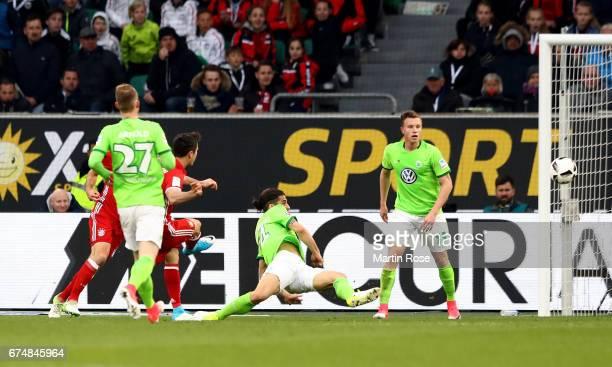 Robert Lewandowski of Muenchen is scoring the 2nd goal the Bundesliga match between VfL Wolfsburg and Bayern Muenchen at Volkswagen Arena on April 29...