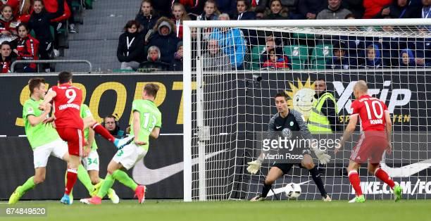 Robert Lewandowski of Muenchen is scoring the 3rd goal the Bundesliga match between VfL Wolfsburg and Bayern Muenchen at Volkswagen Arena on April 29...