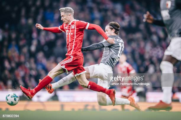 Robert Lewandowski of Muenchen is tackled by Michael Gregoritsch of Augsburg during the Bundesliga match between FC Bayern Muenchen and FC Augsburg...