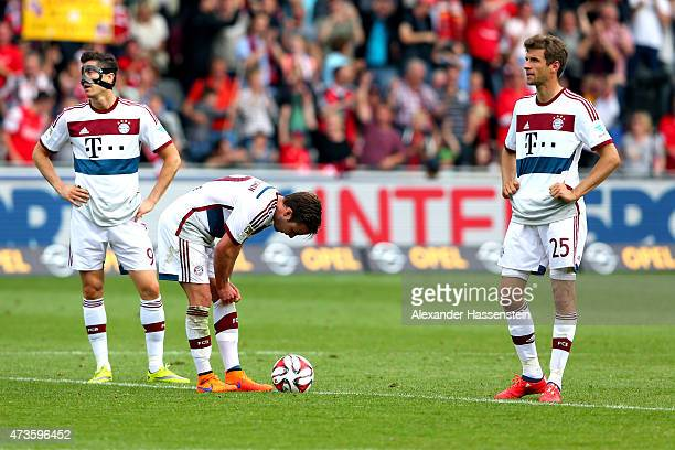 Robert Lewandowski of Muenchen reacts with his team mates Mario Goetze and Thomas Mueller after receiving the second goal during the Bundesliga match...