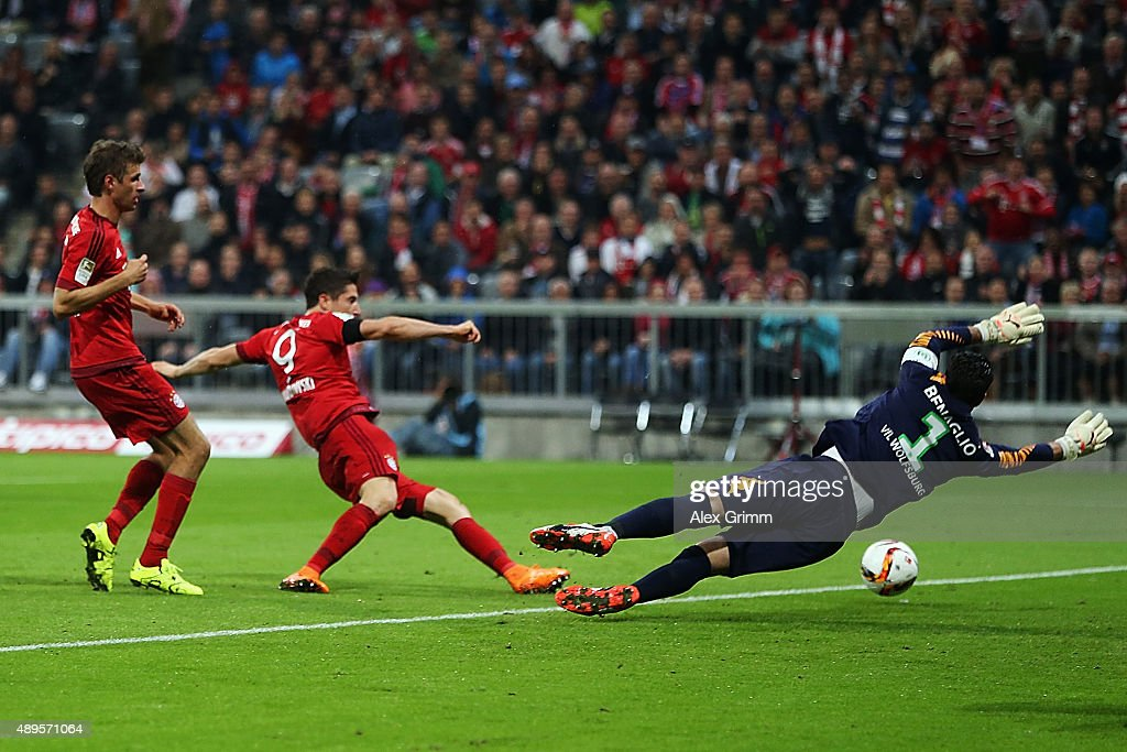 <a gi-track='captionPersonalityLinkClicked' href=/galleries/search?phrase=Robert+Lewandowski&family=editorial&specificpeople=5532633 ng-click='$event.stopPropagation()'>Robert Lewandowski</a> of Muenchen scores his team's first goal against goalkeeper <a gi-track='captionPersonalityLinkClicked' href=/galleries/search?phrase=Diego+Benaglio&family=editorial&specificpeople=543817 ng-click='$event.stopPropagation()'>Diego Benaglio</a> of Wolfsburg during the Bundesliga match between FC Bayern Muenchen and VfL Wolfsburg at Allianz Arena on September 22, 2015 in Munich, Germany.