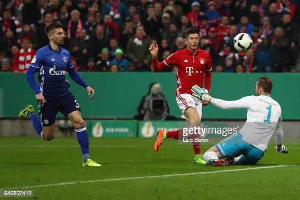Robert Lewandowski of Muenchen scores his team's first goal past goalkeeper Ralf Faehrmann and Matija Nastasic of Schalke during the DFB Cup quarter...