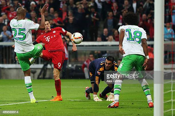 Robert Lewandowski of Muenchen scores his team's third goal against Naldo Dante and goalkeeper Diego Benaglio of Wolfsburg during the Bundesliga...