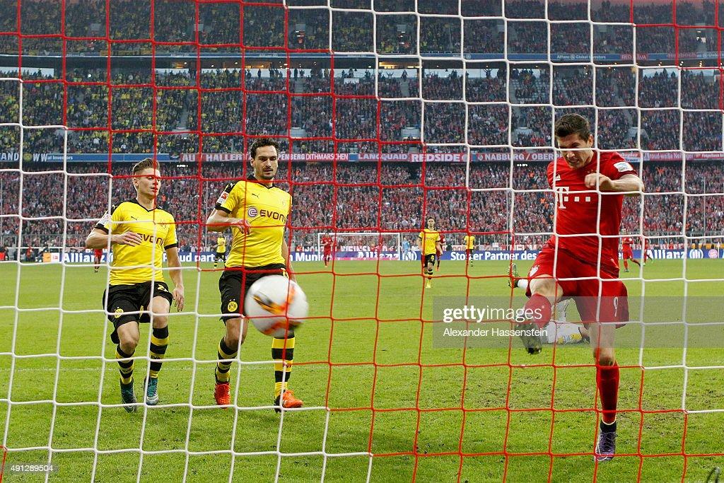 Robert Lewandowski of Muenchen scores the 3rd team goal against Mats Hummels of Dortmund and his team mate Lukasz Piszczek during the Bundesliga...