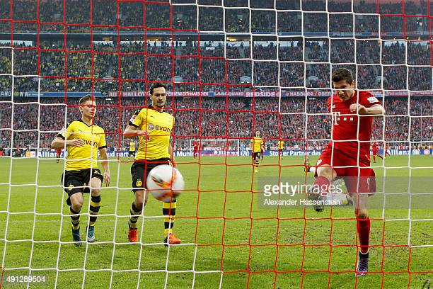 Robert Lewandowski of Muenchen scores the 3rd team goal against Mats Hummels of Dortmund and his team mate Lukasz Piszczek during the Bundesliga...