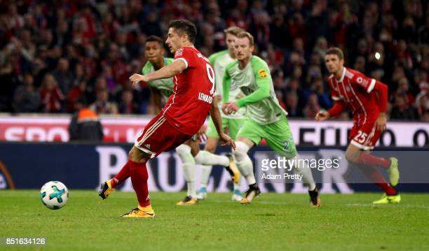 Robert Lewandowski of Muenchen scores the opening goal by penalty kick during the Bundesliga match between FC Bayern Muenchen and VfL Wolfsburg at...