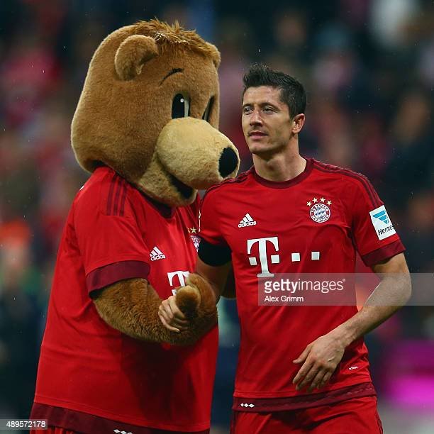 Robert Lewandowski of Muenchen shakes hands with mascot Berni after the Bundesliga match between FC Bayern Muenchen and VfL Wolfsburg at Allianz...