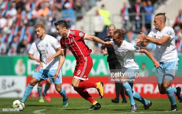 Robert Lewandowski of Muenchen vies with Fabio Leutenecker Julius Reinhardt and Maurice Trapp of Cottbus during the DFB Cup first round match between...