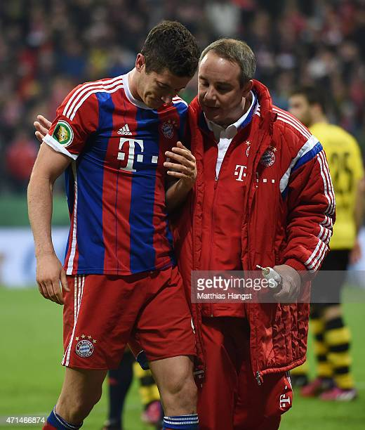 Robert Lewandowski of Muenchen walks off the pitch next to doctor Volker Braun during the DFB Cup Semi Final match between FC Bayern Muenchen and...