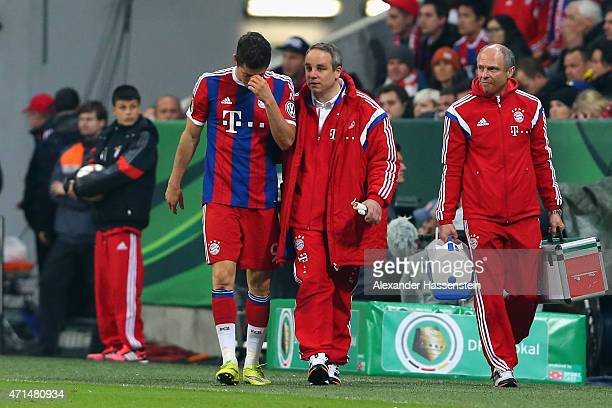 Robert Lewandowski of Muenchen walks with team doctor Volker Braun during the DFB Cup Semi Final match between FC Bayern Muenchen and Borussia...