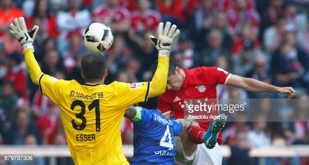 Robert Lewandowski of Munich vie for the ball against goalkeeper Michael Esser and Aytac Sulu of Darmstadt during the Bundesliga first division...