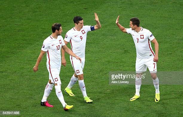 Robert Lewandowski of Poland celebrates scoring his team's first goal with his team mates Grzegorz Krychowiak and Arkadiusz Milik during the UEFA...