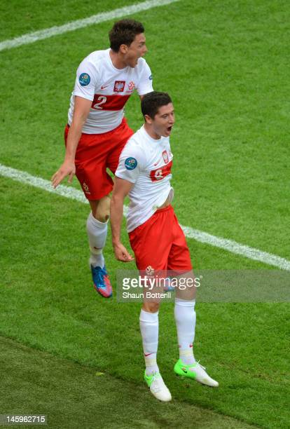Robert Lewandowski of Poland celebrates scoring the opening goal with Sebastian Boenisch of Poland during the UEFA EURO 2012 Group A match between...