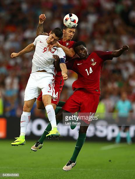 Robert Lewandowski of Poland competes for the ball against Jose Fonte and William Carvalho of Portugal during the UEFA EURO 2016 quarter final match...