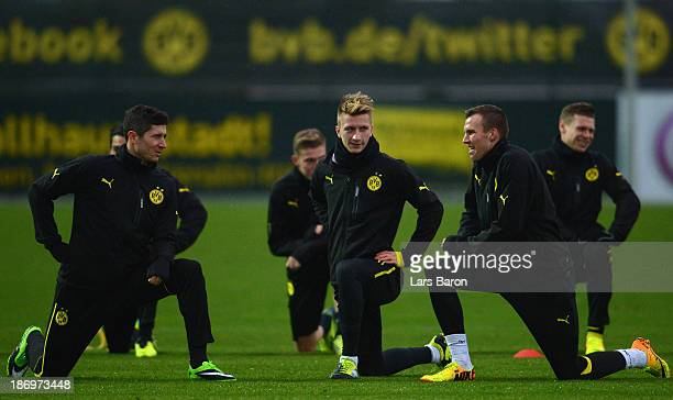 Robert Lewandowski streches next to Marco Reus and Kevin Grosskreutz during a Borussia Dortmund training session ahead of the UEFA Champions League...