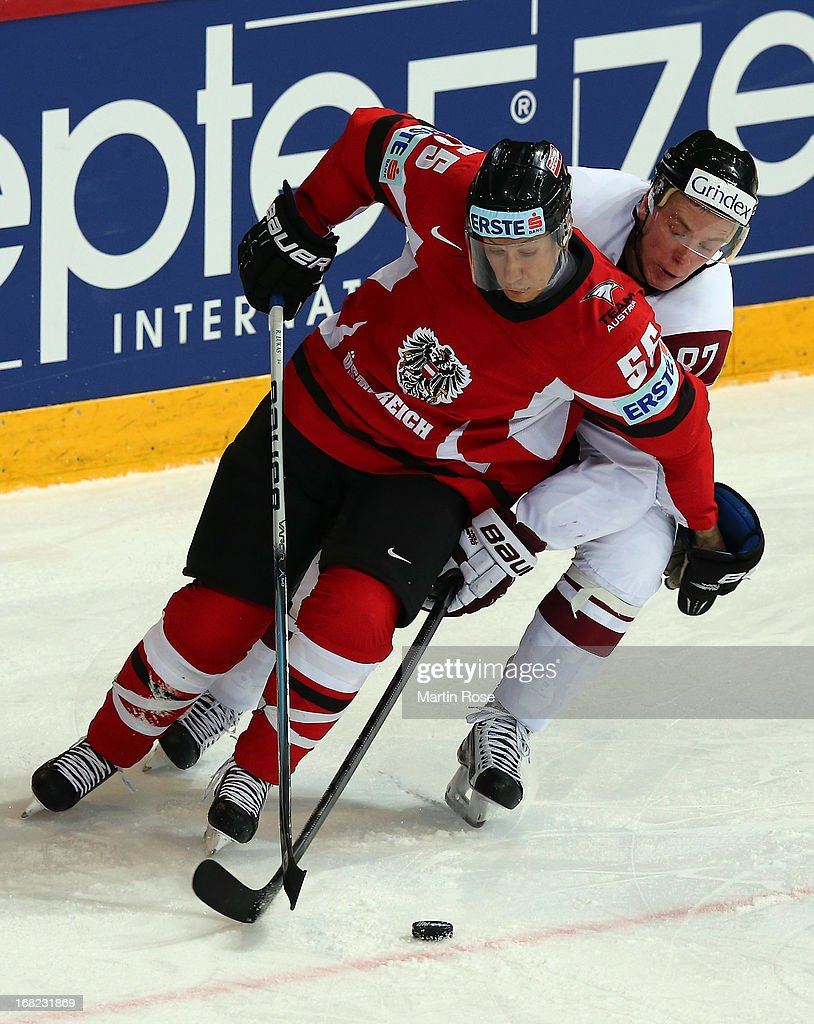 Robert Lukas (L) of Austria and GInts Meija (R) of Latvia battle for the puck during the IIHF World Championship group H match between Austria and Latvia at Hartwall Areena on May 7, 2013 in Helsinki, Finland.