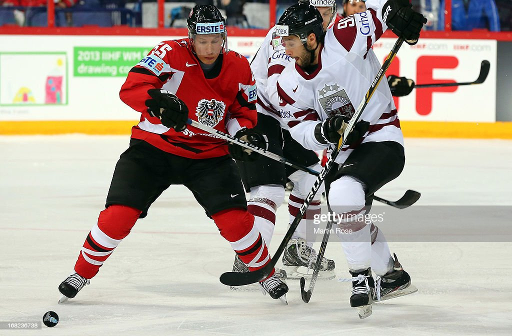 Robert Lukas (L) of Austria and Koba Jass (R) of Latvia battle for the puck during the IIHF World Championship group H match between Austria and Latvia at Hartwall Areena on May 7, 2013 in Helsinki, Finland.