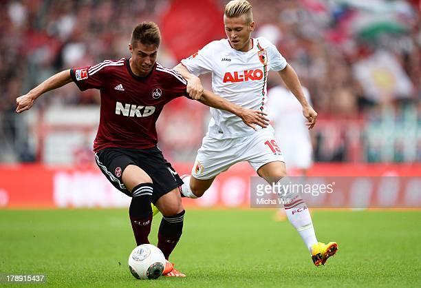 Robert Mak of Nuernberg is challenged by Matthias Ostrzolek of Augsburg during the Bundesliga match between 1 FC Nuernberg and FC Augsburg at Grundig...