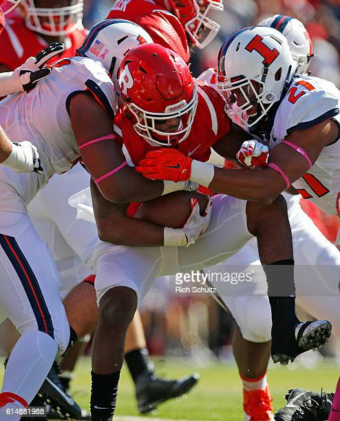 Robert Martin III is tackled by Dawuane Smoot and Patrick Nelson of Illinois during the first quarter of a game on October 15 2016 in Piscataway New...