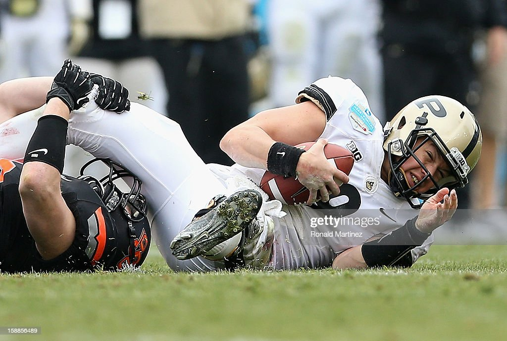 Robert Marve #9 of the Purdue Boilermakers is tackled by Caleb Lavey #45 of the Oklahoma State Cowboys during the Heart of Dallas Bowl at Cotton Bowl on January 1, 2013 in Dallas, Texas.
