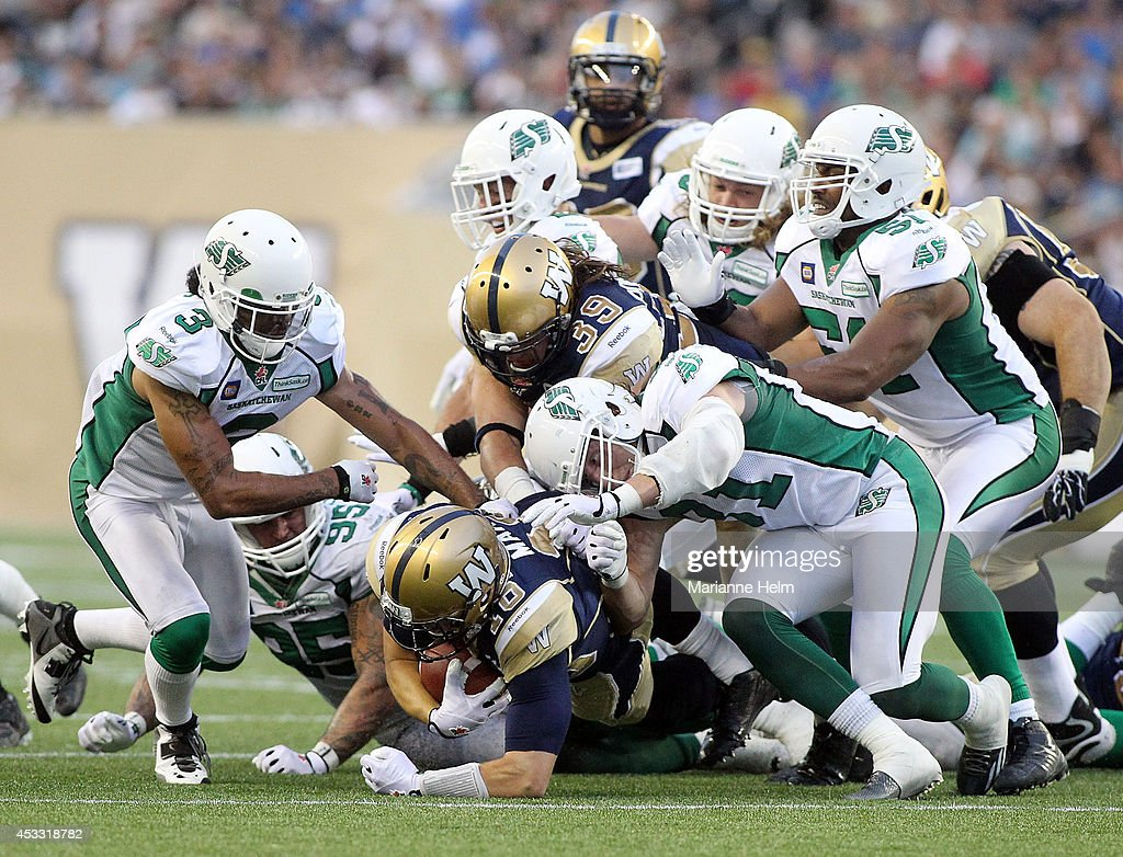 Robert Marve #16 of the Winnipeg Blue Bombers gets past the Saskatchewan Roughriders for a five yard gain for a first down in first half action in a CFL game at Investors Group Field on August 7, 2014 in Winnipeg, Manitoba, Canada.