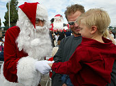 Robert Maxim as Santa Claus greets Bailey Baker and his dad James at a ceremony marking the completion of the Santa Statue restoration project in...