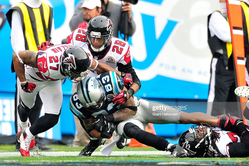 Robert McClain #27 and Thomas DeCoud #28 of the Atlanta Falcons stop Louis Murphy #83 of the Carolina Panthers short of a first down during play at Bank of America Stadium on December 9, 2012 in Charlotte, North Carolina.