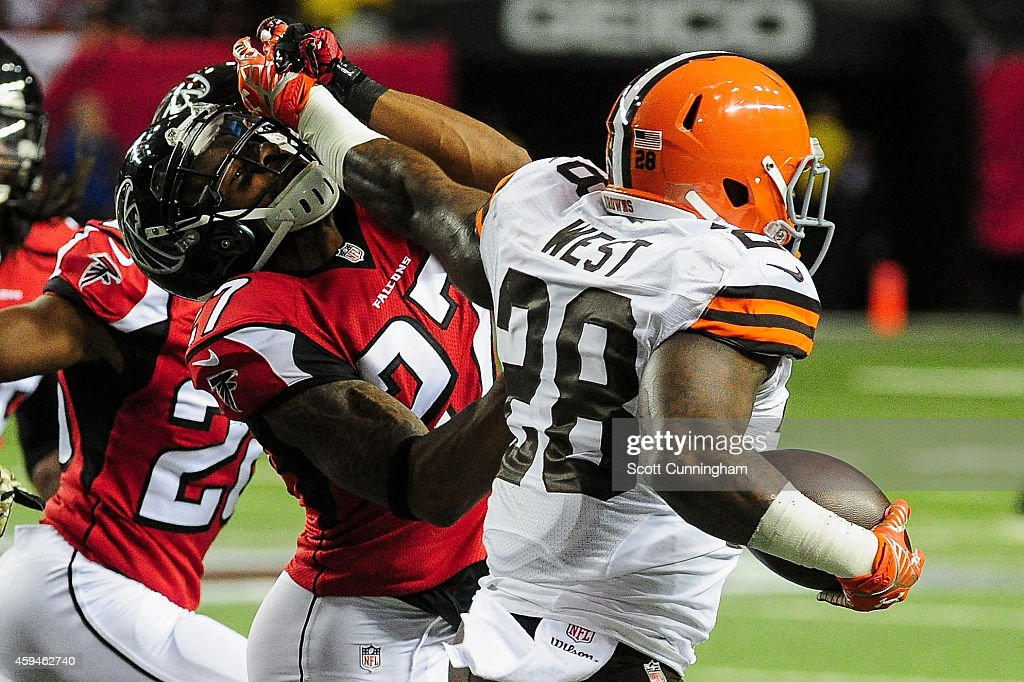 Robert McClain #27 of the Atlanta Falcons is stiff armed by Terrance West #28 of the Cleveland Browns in the first half at Georgia Dome on November 23, 2014 in Atlanta, Georgia.