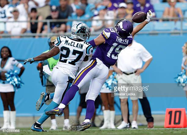 Robert McClain of the Carolina Panthers watches as Adam Thielen of the Minnesota Vikings makes a catch during their game at Bank of America Stadium...
