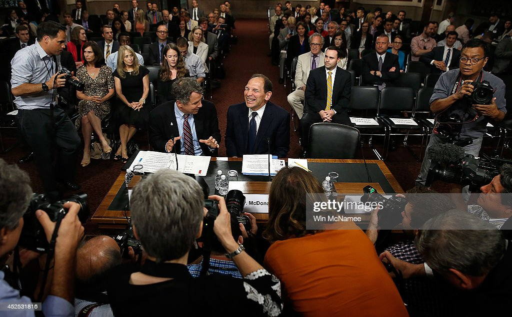 Robert McDonald (R), President Obama's nominee to be the Secretary of Veterans Affairs, laughs while talking with Sen. <a gi-track='captionPersonalityLinkClicked' href=/galleries/search?phrase=Sherrod+Brown&family=editorial&specificpeople=3986311 ng-click='$event.stopPropagation()'>Sherrod Brown</a> (L) (D-OH) prior to McDonald's testimony before the Senate Veterans Affairs Committee July 22, 2014 in Washington, DC. McDonald, if confirmed, would lead the recently scandal plagued Department of Veterans Affairs.