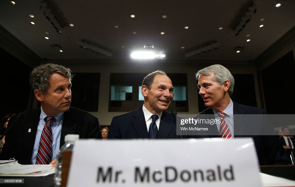 Robert McDonald (C), President Obama's nominee to be the Secretary of Veterans Affairs, confers with Sen. <a gi-track='captionPersonalityLinkClicked' href=/galleries/search?phrase=Sherrod+Brown&family=editorial&specificpeople=3986311 ng-click='$event.stopPropagation()'>Sherrod Brown</a> (L) (D-OH) and Sen. <a gi-track='captionPersonalityLinkClicked' href=/galleries/search?phrase=Rob+Portman&family=editorial&specificpeople=226973 ng-click='$event.stopPropagation()'>Rob Portman</a> (R) (R-OH) prior to McDonald's testimony before the Senate Veterans Affairs Committee July 22, 2014 in Washington, DC. McDonald, if confirmed, would lead the recently scandal plagued Department of Veterans Affairs.