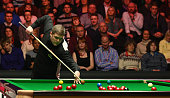 Robert Milkins of England plays a shot during his first round match against Neil Robertson of Australia on day Two of the 2015 Dafabet Masters at...
