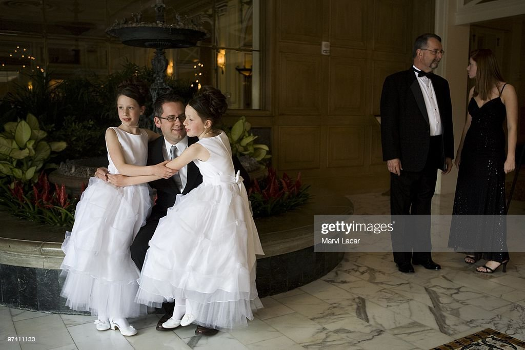 Robert Moore poses for a photograph with his 9-year-old twin daughters Lauren and Elizabeth on May 16, 2008 in Colorado Springs, Colorado. The annual Father-Daughter Purity Ball, founded in 1998 by Randy and Lisa Wilson, focuses on the idea that a trustworthy and nurturing father will influence his daughter to lead a lifestyle of 'integrity and purity.'