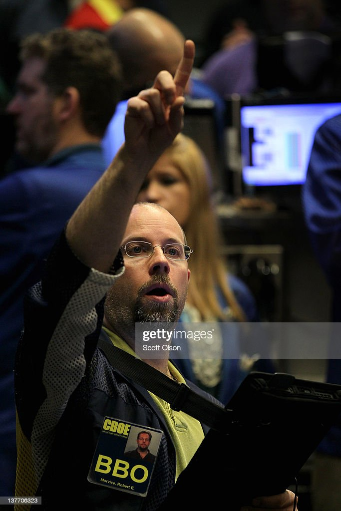 Robert Morvice signals an offer in the Standard & Poor's 500 stock index options pit at the Chicago Board Options Exchange (CBOE) following the Federal Open Market Committee meeting on January 25, 2012 in Chicago, Illinois. Following the meeting the Fed, which left interest rates unchanged, said it does not plan any rate changes until late 2014.