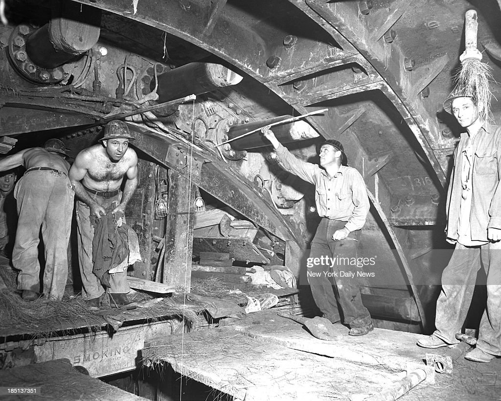 Robert Moses director of city's scrap drive proposed to halt construction of the BrooklynBattery tunnel Here Sandhog Everett Elliott measures...