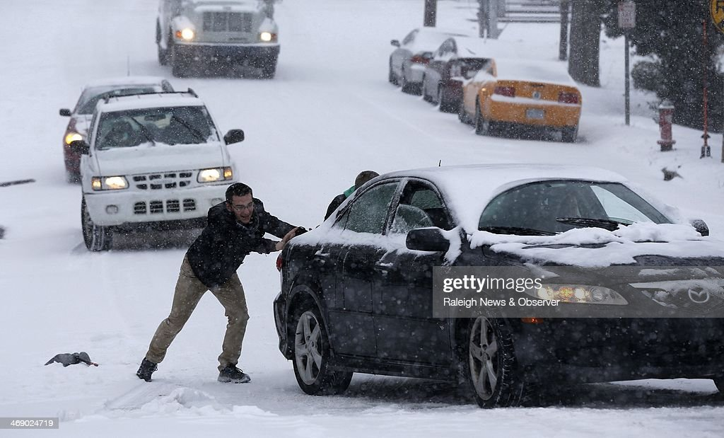 Robert Moss, left, and Isaac Granick (behind car) help Dan Schneider navigate his car up W. Hargett St. in the snow in Raleigh, N.C., Wednesday, Feb. 12, 2014.