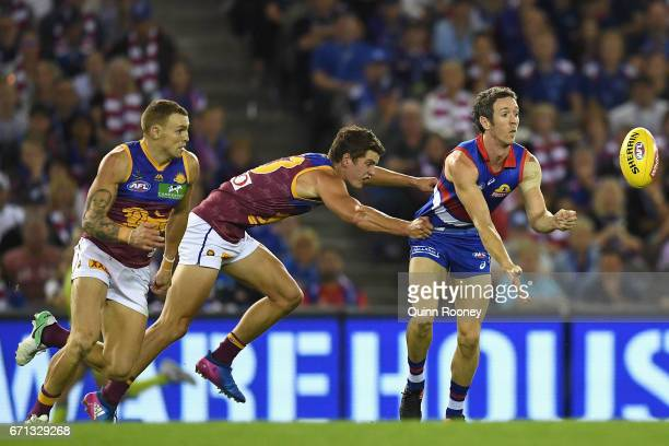 Robert Murphy of the Bulldogs handballs whilst being tackled by Jarrod Berry of the Lions during the round five AFL match between the Western...