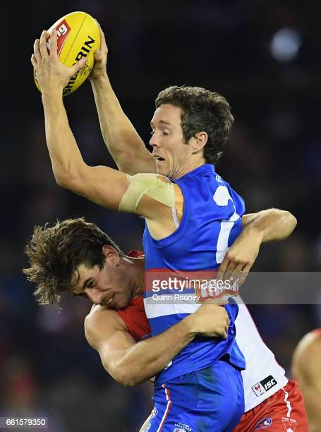 Robert Murphy of the Bulldogs is tackled by Jake Lloyd of the Swans during the round two AFL match between the Western Bulldogs and the Sydney Swans...