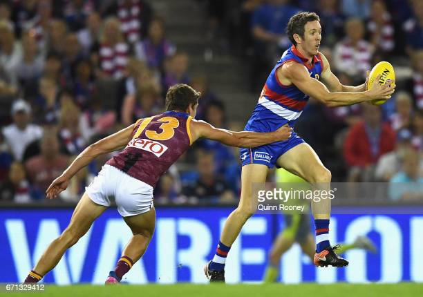 Robert Murphy of the Bulldogs is tackled by Jarrod Berry of the Lions during the round five AFL match between the Western Bulldogs and the Brisbane...