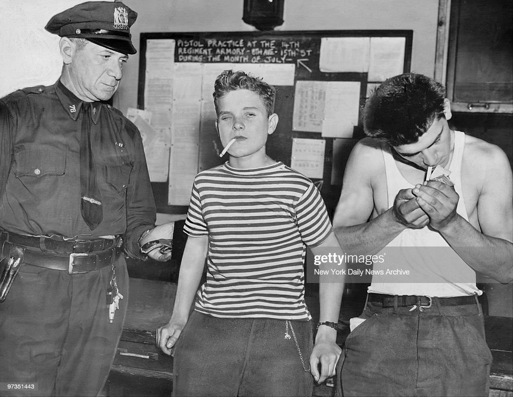 Robert Naschak (center), 16, of Irvington, N.J, who calls himself Curly Bill, and Ralph Yamicello, 20, who are being held at the Bergen St. station on stickup charges.
