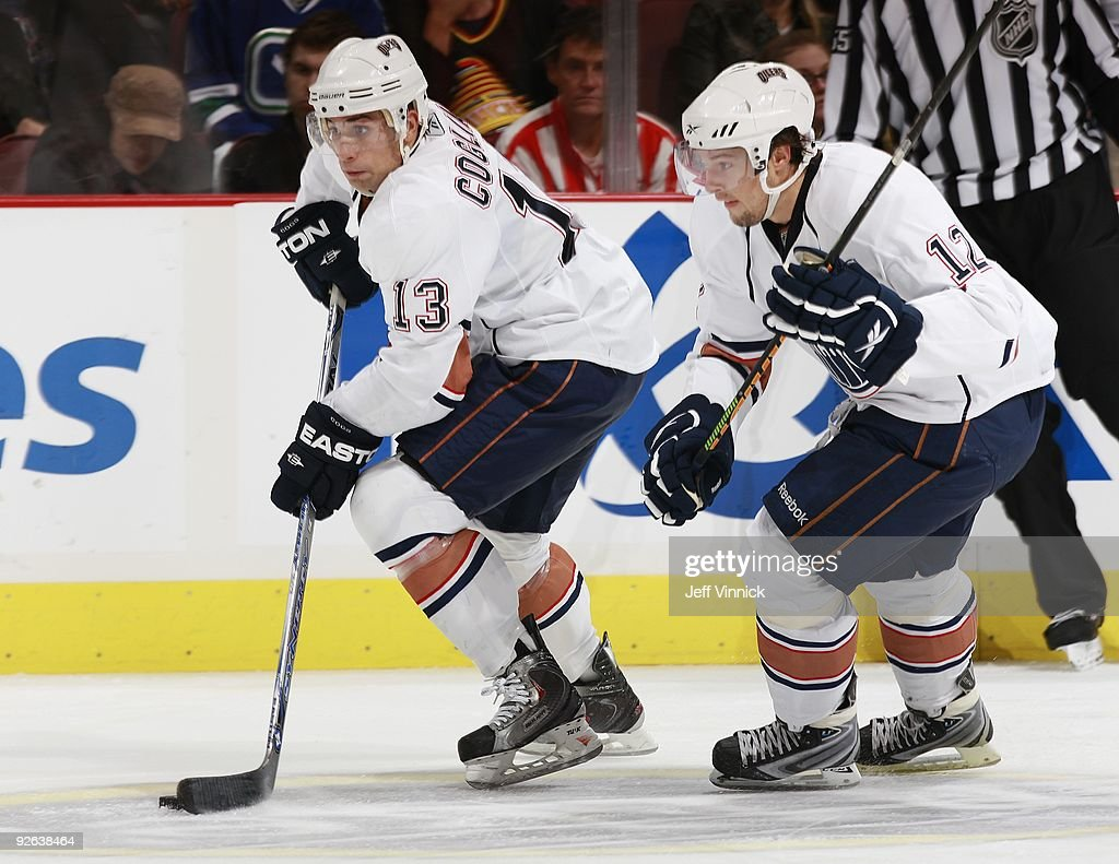 Robert Nilsson of the Edmonton Oilers looks on as teammate Andrew Cogliano skates up ice with the puck during their game against the Vancouver...