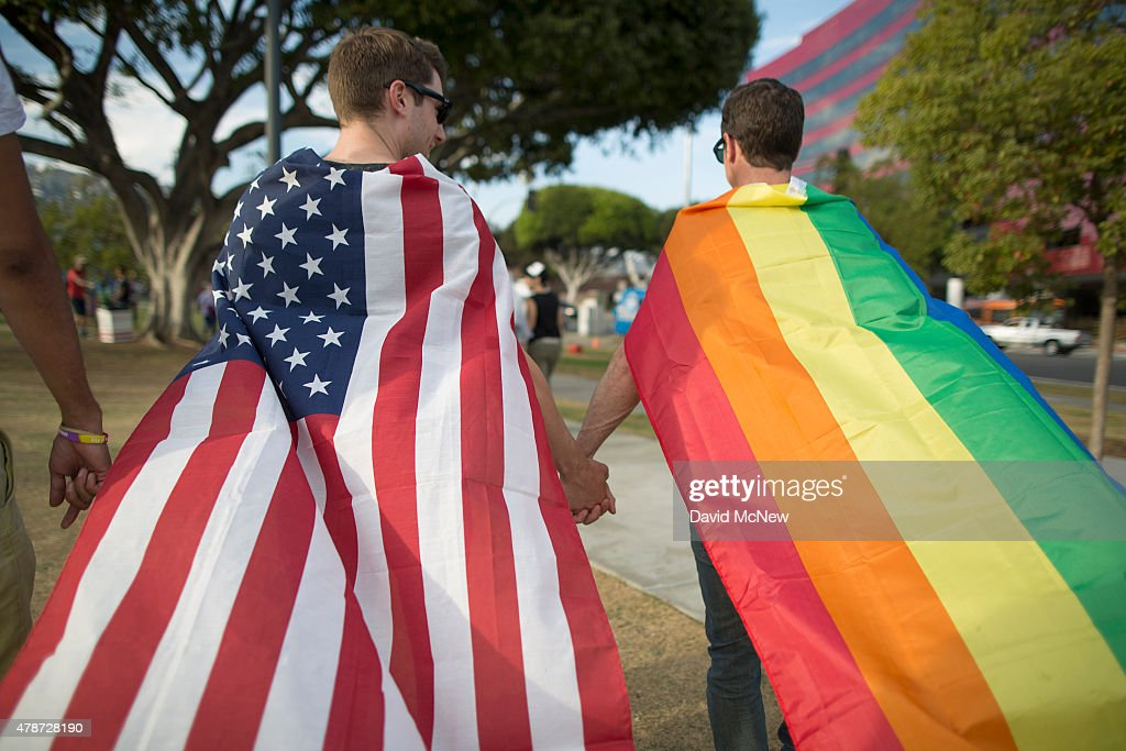 Robert Oliver and Mark Heller hold hands draped in flags as they celebrate the Supreme Court ruling on samesex marriage on June 26 2015 in West...
