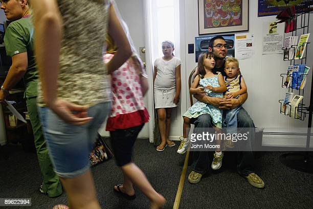 Robert Pacheco holds his chldren while in the waiting room of the Spanish Peaks Outreach Clinic on August 5 2009 in Walsenburg Colorado Pacheco who...