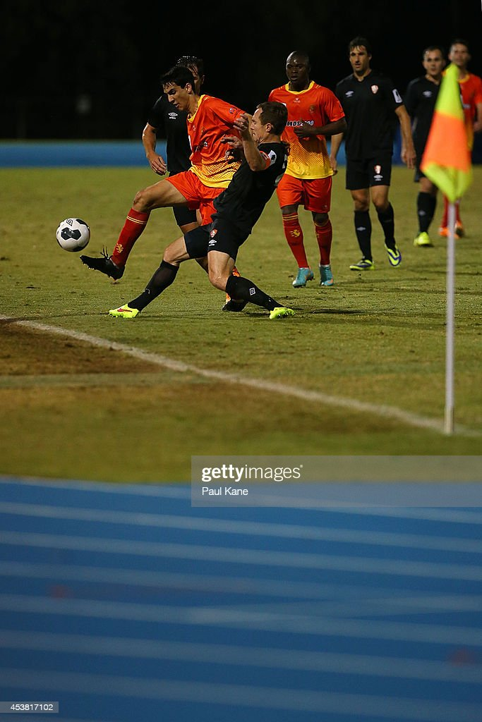 Robert Petkov of the Lions and Matthew Smith of the Roar contest for the ball during the FFA Cup match between the Stirling Lions and the Brisbane Roar at Western Australia Athletics Stadium on August 19, 2014 in Perth, Australia.