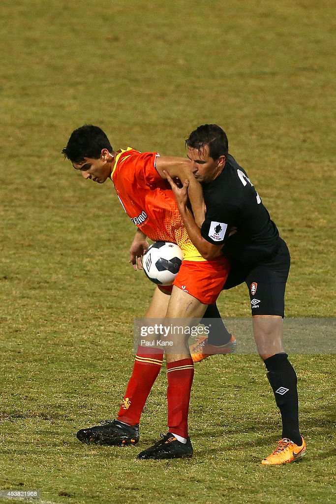 Robert Petkov of the Lions is challenged by Shane Steffanutto of the Roar during the FFA Cup match between the Stirling Lions and the Brisbane Roar at Western Australia Athletics Stadium on August 19, 2014 in Perth, Australia.