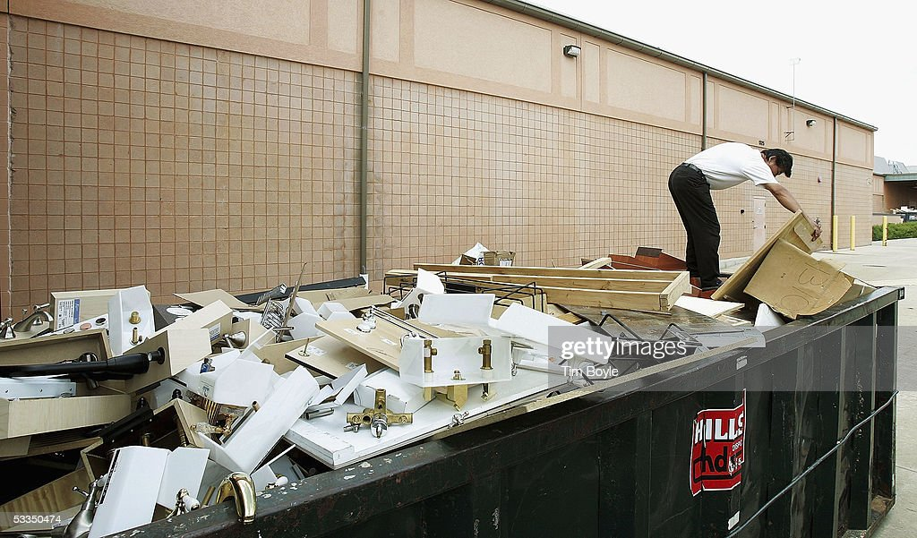 Robert Phan scavenges through a dumpster for discarded items behind a closed Expo Design Center store August 10, 2005 in Schaumburg, Illinois. Home Depot has said it plans to close a third of its Expo Design Centers in the US, closing three of its five stores in the Chicago area.