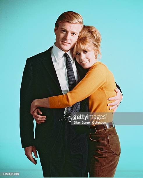 Robert Redford US actor and Jane Fonda US actress cuddling as they pose for a studio portrait against a light blue background issued as publicity for...