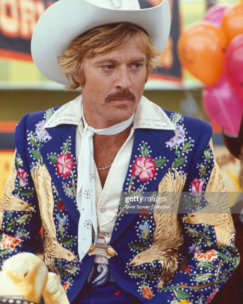 Robert Redford US actor wearing a brightly coloured Westernstyle jacket embroidered with floral motifs a white cowboy hat and white neckerchief in a...